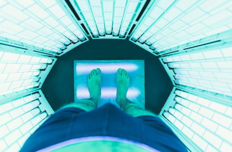Man getting tan in a uv tanning device in ottawa tanning salon