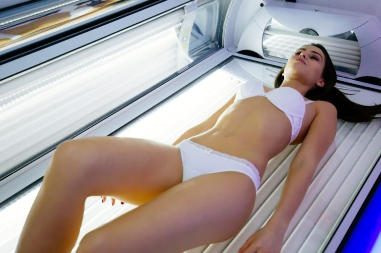 Beautiful sexy woman tanning in UV tanning device